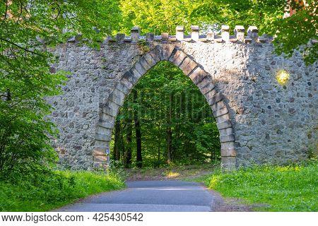 Gothic Arc Gate Over Asphalt Road In The Forest. Arturs Castle Near Sychrov, Czech Republic