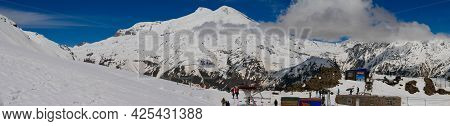 Mount Elbrus, Russia - May 10, 2021: Panoramic View Of Mount Elbrus With Snow-capped Peaks Against T