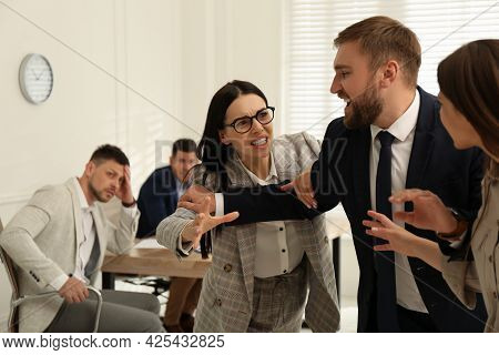 Man Interrupting Colleagues Fight At Work In Office