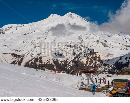 Mount Elbrus, Russia - May 10, 2021: View Of Mount Elbrus With Snow-capped Peaks Against The Blue Sk