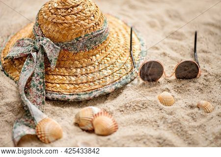 Straw Hat And Sunglasses Left On The Sandy Beach In Summer Holiday