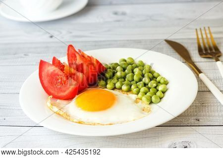 Fried Egg With Green Peas And Tomatoes On Light Background. Healthy Breakfast.