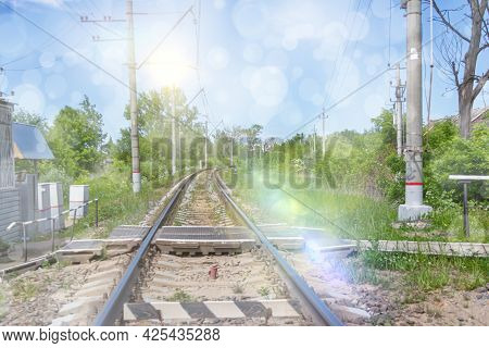 The Railway Going Away Into The Distance. Railroad Crossing With Green Trees And Blue Sky In Summer.