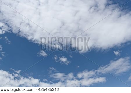 Blue Summer Sky Covered With White Clouds. Fluffy White Clouds Float Across The Sky On A Clear Day W