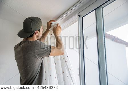 Young Man Installing Curtains Over Window At Home