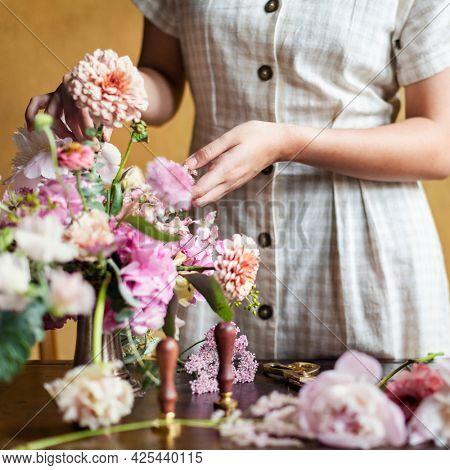 Florist adding pip salmon to a vase