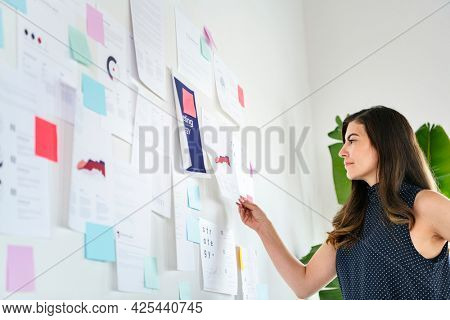 Businesswoman presenting a marketing strategy on a white wall