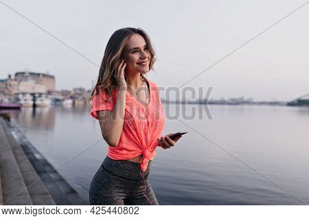 Good-humoured Girl Listening Music After Training. Attractive Female Runner Posing Near River With S
