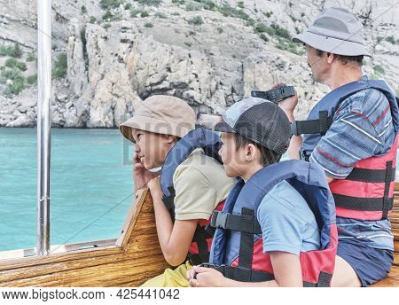 Grandfather And His Two Grandsons, In Life Jackets Trip On Pleasure Boat On The Sea. Asian Older Man