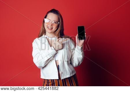 Model In Sun Glasses Looks At The Camera And Smiles, Summer Mood. The Girl Points To The Phone In He