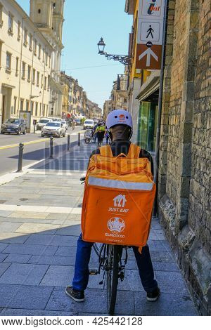 May 2021 Parma, Italy: Courier On Bike With Special Orange Backpack With Just Eat Logo Icon Close-up