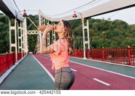 Shapely Lady Drinking Water During Marathon. Outdoor Portrait Of Happy Female Runner Standing At Cin