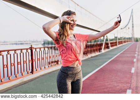 Shapely Blonde Woman Making Selfie At Stadium. Outdoor Portrait Of Excited Girl Taking Picture Of He