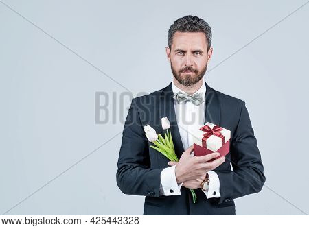 Elegant Tuxedo Man Hold Present Box And Tulips. Spring Flowers. Floral Shop. Gift Store.