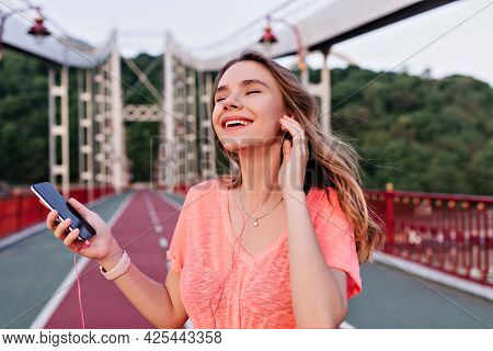 Graceful European Lady Listening Favorite Song With Eyes Closed While Posing At Stadium. Winsome Gir