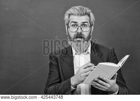 Teacher With Textbook. Experienced Teacher. Selecting Appropriate Courses. Teacher With Book Explain