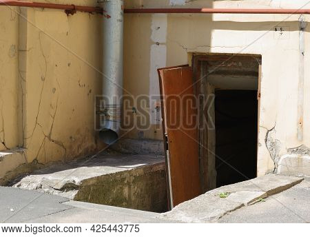 Broken Open Brown Door To The Basement Of An Apartment Building