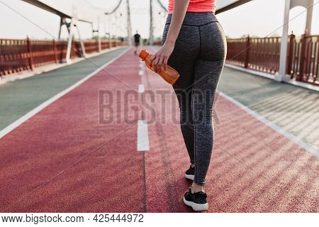 Young Woman In Gray Pants Standing On Cinder Track With Bottle. Charming Female Runner Waiting For M