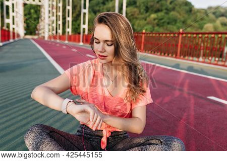 Dreamy Sporty Girl Looking At Her Watch After Training. Outdoor Shot Of Refined Woman Relaxing Befor
