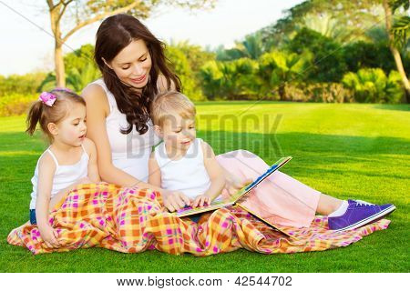 Photo of young mother with two cute kids reading book outdoors in spring time, happy mom teaching her children in the park, day care, beautiful woman with son and daughter having fun on backyard