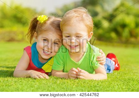 Image of two happy children having fun in the park, brother and sister lying down on green grass, best friends playing outdoors in spring, adorable little girl with cute boy enjoying springtime nature