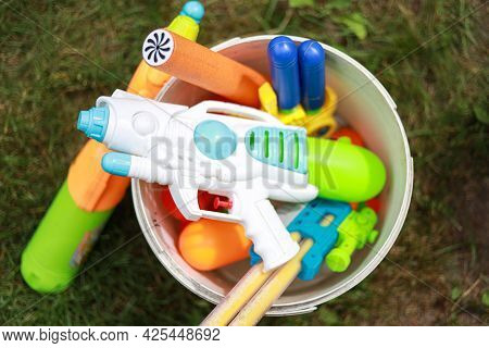 Upper View With Different Water Toys Pistols Guns For Kids Toddlers. One Water Pistol In Foreground.