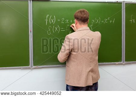 A Math Teacher Shows Students The Solution Of A Problem At The School Blackboard.