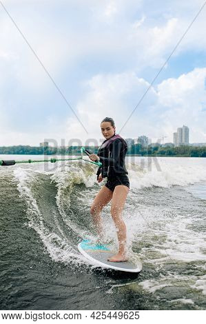 Young Woman Wakesurfing On River Is Towed Behind A Motorboat By Wire Rope.