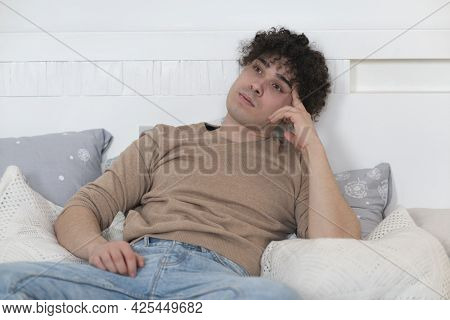 Portrait Of Pensive Thoughtful Dreamy Lazy Bored Guy, Young Handsome Curly Ethnic Man Is Lying On Be
