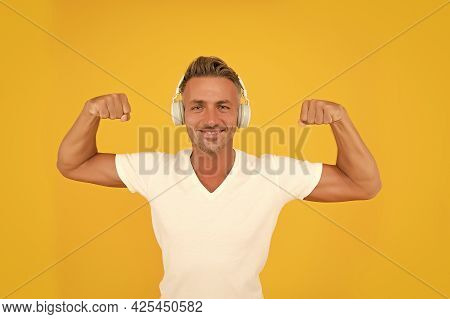 Happy Athletic Man Listen To Music In Headphones Flexing Strong Arms Yellow Background, Strength