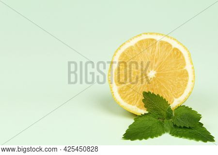 Lemon And Fresh Mint Leaves Are Herbs On A Delicate Mint Background.the Concept Of Summer Citrus Dri