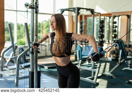 Sport Slim Fit Woman In Sportswear Exercising Building Muscles With  Cable Crossover Machine In  Mod