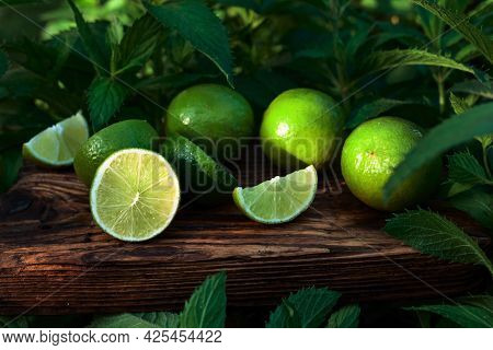 Limes And Growing Mint In The Garden. Lime Slices And Mint Leaves On An Old Wooden Background.