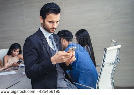 Handsome Businessman Standing Using Mobile Phone While Taking A Break During A Conference Room Meeti