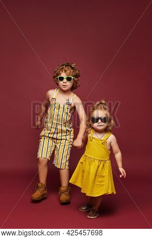 Cute Little Fashionable Children Over A Pink Background, Isolated. Cute Little Girl And Curly Boy In