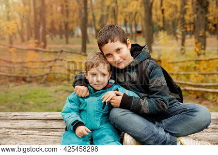 Funny Brothers Who Are Smiling Happily Together. Two Happy Boys In The Woods. Two Brothers Play Outd