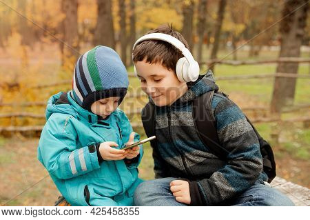 Pretty Preteen Boy With His Younger Brother Looking On The Screen Of Mobile, Lifestyle, Happy Childh