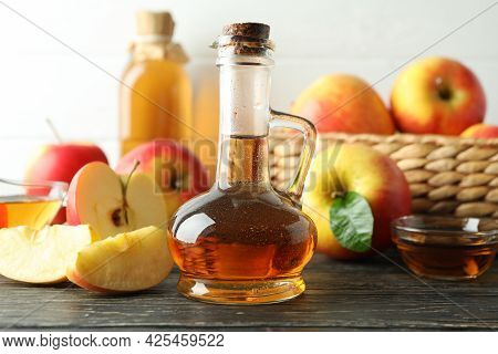 Homemade Apple Vinegar And Ingredients On Wooden Table