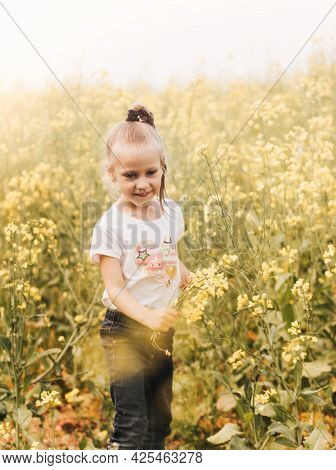 Little Pretty Girl With Canola Flowers On The Field In Summer. Summer Holiday Season. Carefree Child