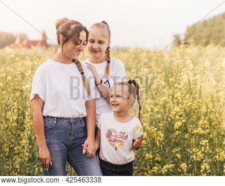 Mom With Two Daughters Walks On The Field With Canola Flowers In Summer