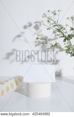 Business Card Or Invitation Mockup On A Pedestal With A Branch Of Chamomile. Fashionable Creative Fo