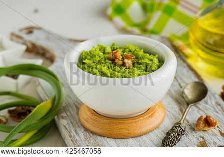 Garlic Arrow Pesto Sauce With Walnuts In A White Mortar On A Light Concrete Background. Sauce Recipe
