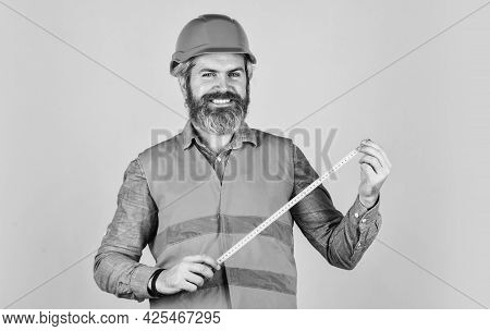 Yellow Colored Measuring Tape. Bearded Man In Hardhat. Brutal Hipster Worker Use Tape Measure. Man I