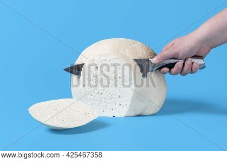 Woman Hand Slicing From A Big Block Of Cheese. Chunk Of Romanian Cheese Isolated On A Blue Backgroun