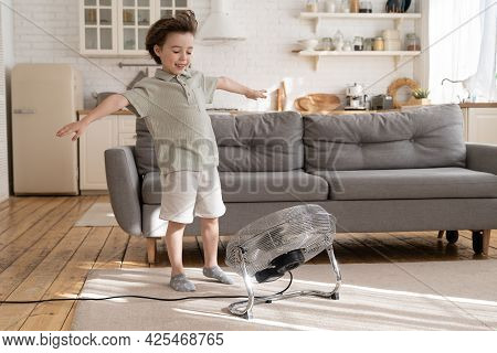 Overjoyed Small Kid, Preschool Boy Has Fun With Blowing Ventilator Equipment And Strong Fresh Air Fl