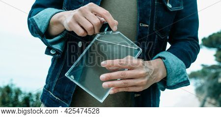 a young man, wearing a denim jacket and a casual green t-shirt, is unscrewing the cap of a rectangular reusable water bottle outdoors, in a panoramic format to use as web banner or header