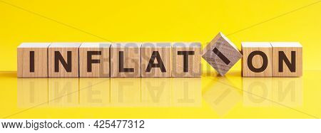Inflation Word Is Made Of Wooden Building Blocks Lying On The Yellow Table, Concept