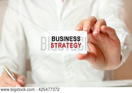 A Woman In A White Shirt Holds A Piece Of Paper With The Text: Business Strategy. Business Concept.