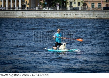 Saint-petersburg, Russia, 26.06.2021. A Man Swims Along The Neva River On A Surfboard With His Dog.