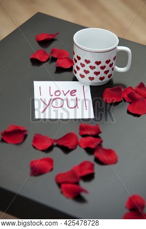 Love Letter, Rose Petals And A White Cup With Hearts On A Dark Coffee Table, Maybe For A Valentine`s